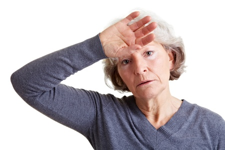hand on forehead: Exhausted old senior woman holding hand to her forehead