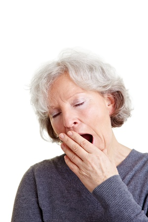 bored face: Old senior woman yawning with hand in front of her mouth Stock Photo