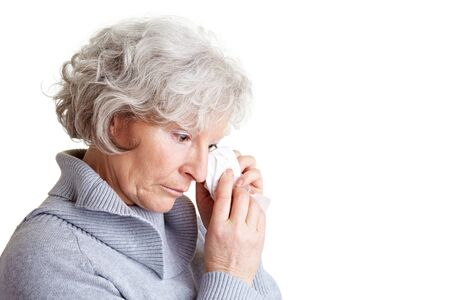 cutout old people: Old senior woman crying and drying her tears with a handkerchief