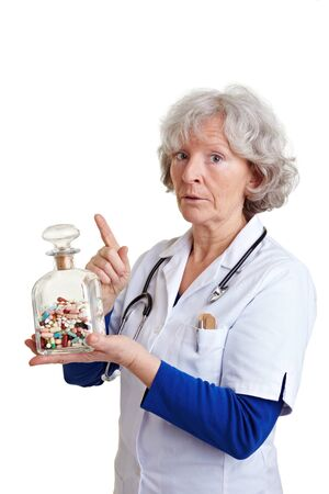 adverse reaction: Elderly female physician warning with many pills in her hand