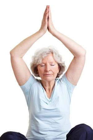 Calm senior woman doing relaxing yoga exercises photo