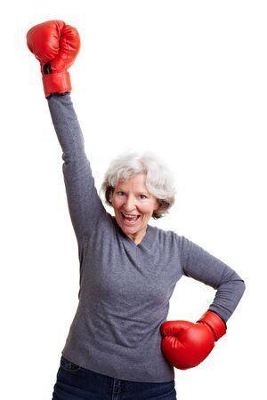 mujeres peleando: Feliz anciana animando con guantes de boxeo rojos