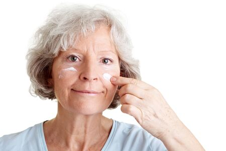 aging skin: Beautiful senior woman applying lotion to her face