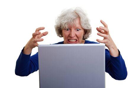 complicación: Mujer senior frustrada gritando a su port�til Foto de archivo