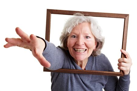 silly face: Happy senior woman reaching through an empty frame