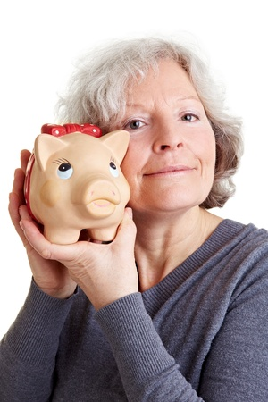 Happy old woman holding a piggy bank to her cheek photo