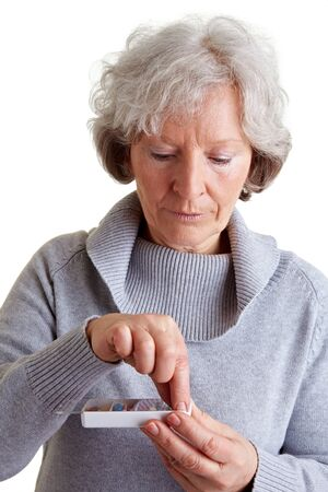 choose person: Old woman taking a pill from a pill dispenser