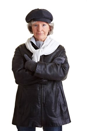 Senior woman standing in winter clothing with scarf and cap photo