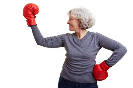 Active elderly woman fighting with red boxing gloves photo