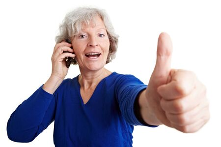 calling on phone: Happy senior woman with mobile phone holding her thumbs up Stock Photo