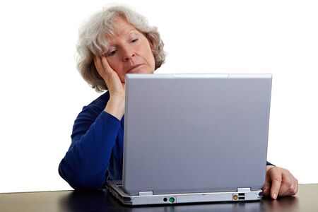 Old woman looking bored at her laptop photo