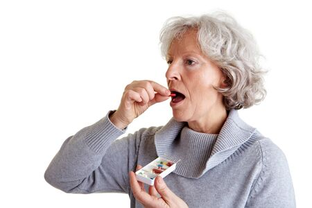 Ill old woman taking a pill from a pill dispenser photo