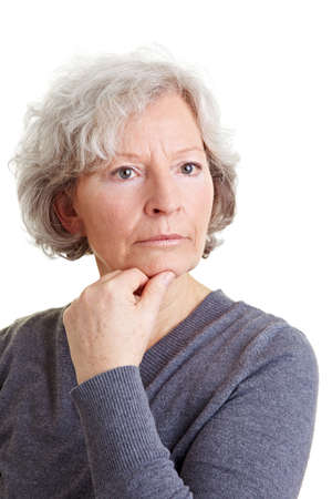 frontal portrait: Pensive old senior woman with hand on her chin