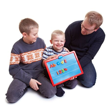 Father teaching his two boys with a magnetic board photo