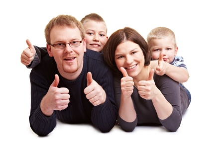 Happy family with two children holding their thumbs up photo