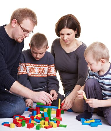 Happy family with two children playing together with building bricks photo