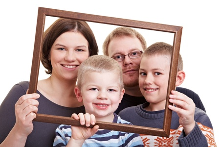 Smiling family with two sons looking through an empty frame photo
