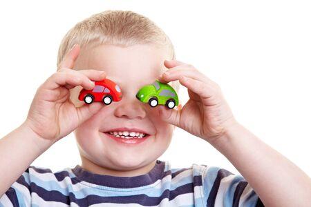 carritos de juguete: Ni�o feliz celebraci�n dos sillas de juguete delante de sus ojos Foto de archivo