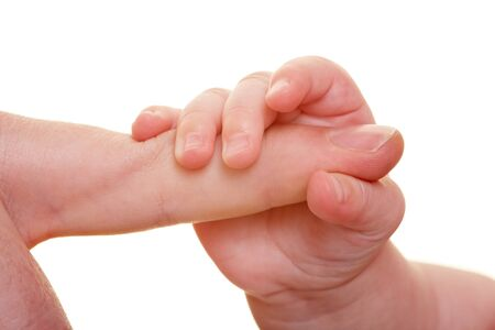 Small baby hand holding big adult finger photo