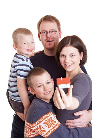 Happy family with two children holding miniature home Stock Photo - 9244051