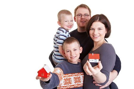 Happy family with two children holding small houses photo