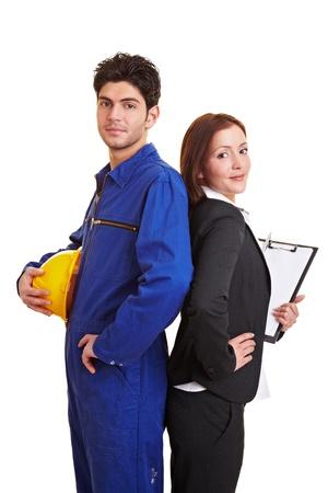 Bedrijfsvrouw en bouwvakker die zich rijtjes bevinden Stockfoto