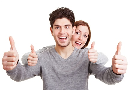 consent: Smiling happy couple holding both thumbs up