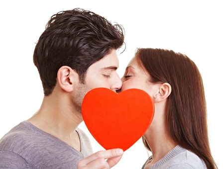 romantic kiss: Happy couple kissing behind a red heart Stock Photo