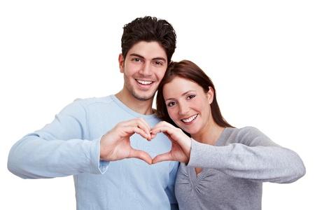 corazon en la mano: Feliz pareja de enamorados que muestra el coraz�n con sus dedos