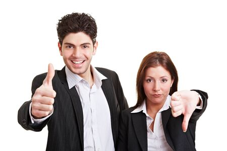 Two young business people holding their thumbs up and down photo