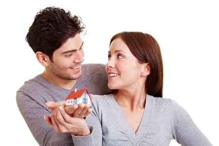 construct: Smiling couple holding a miniature real estate house in their hands Stock Photo