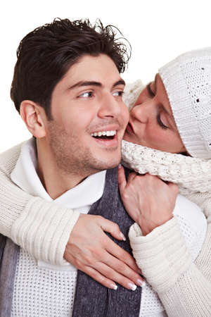Young woman kissing happy man in winter clothes photo