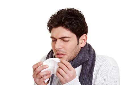 estornudo: Hombre joven con fiebre del heno estornudos en un tejido