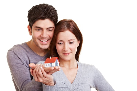sell house: Happy young couple viewing a small house