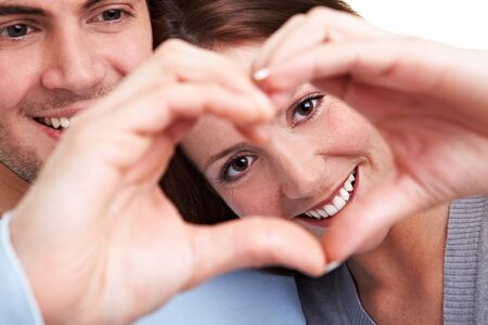 Happy couple in love showing heart with their fingers photo