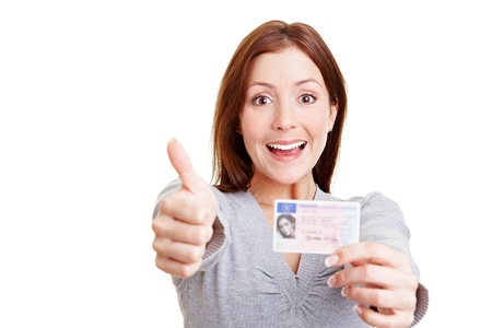 passed test: Happy woman with European driving license holding her thumbs up