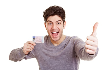 Cheering young man with his Europeandriving license holding a thumb up photo