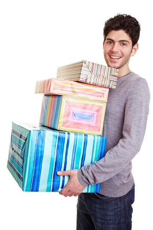 Happy young man carrying many christmas gifts photo