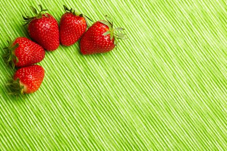 Five strawberries in corner on green background photo
