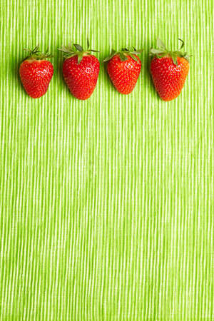 Four fresh strawberries in a row on green background photo
