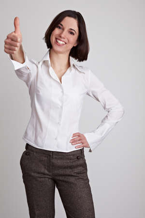 Happy smiling business woman holds her thumb up photo
