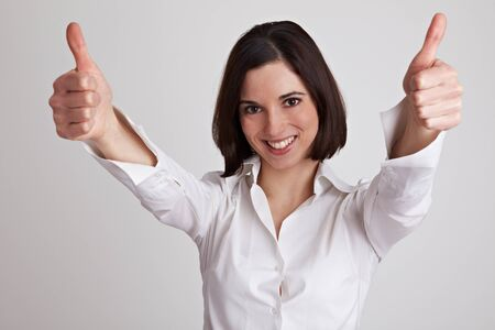 Cheering business woman holds both her thumbs up photo