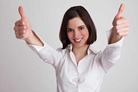ambos: Mujer de negocios divertida sostiene tanto sus pulgares
