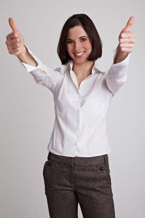 Happy business woman holds two thumbs up photo