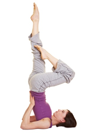 Young woman doing a shoulder stand as yoga exercise Stock Photo - 9515599
