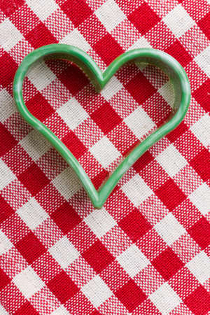 Heart-shaped cookie cutter on a red-white striped tablecloth photo