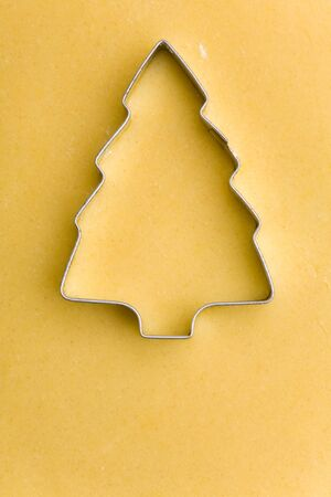 Christmas tree as cookie cutter on raw cookie dough photo