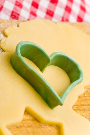 Heart shaped cookie cutter on raw cookie dough photo
