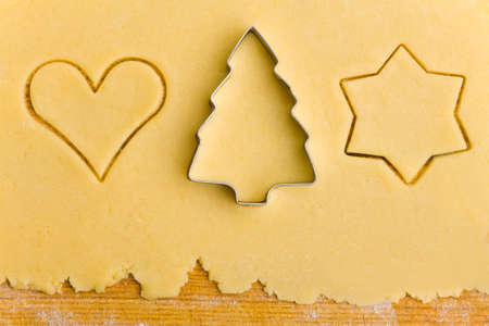 Some christmas cookie cutter shapes on raw cookie dough Stock Photo - 9622105