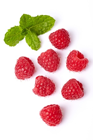 raspberries: Some red ripe raspberries with mint leaves isolated on white